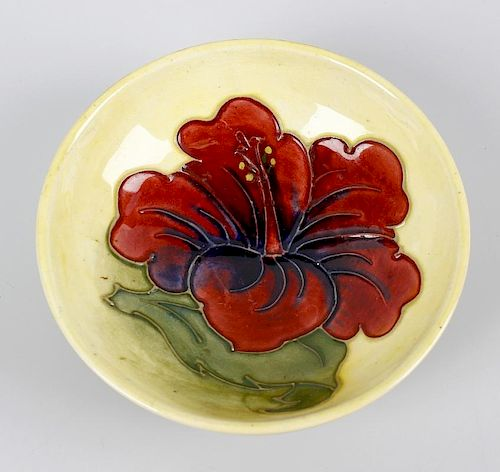 A small Walter Moorcroft dish. Of shallow form having central orchid flower upon a merging pale yell