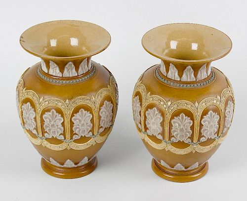 A pair of Doulton Lambeth silicone ware vases. Each of ovoid form with flared neck, having raised fo