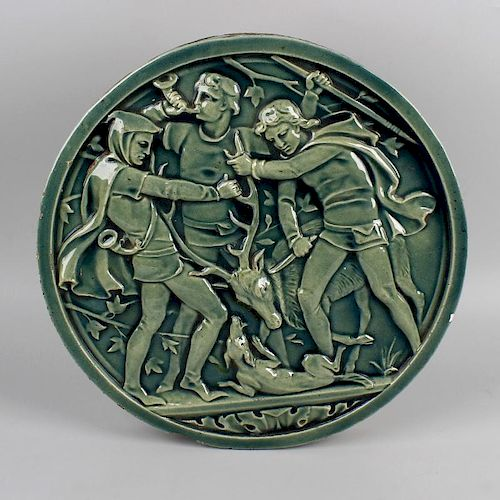 An Arts and Crafts pottery plaque. Of circular form, decorated with raised hunting scene of three fi