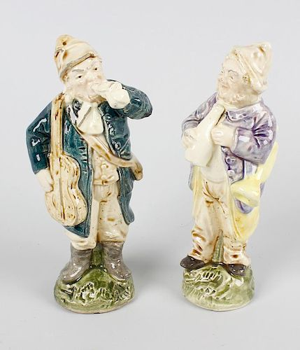 A pair of glazed pottery figures. Each modelled as a male musician carrying a guitar or trumpet and