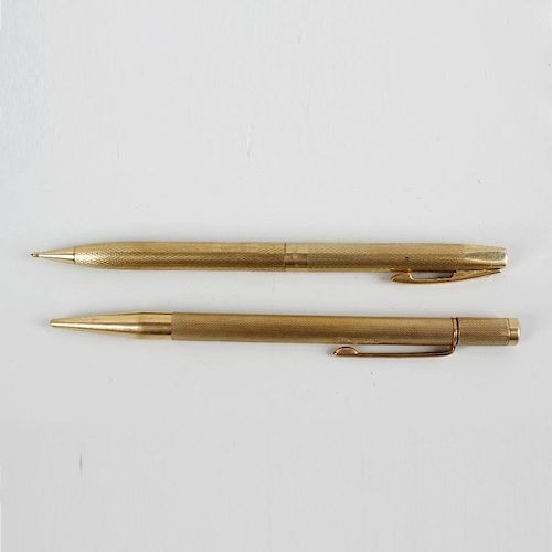 Two 9ct gold mechanical pencils. Comprising a Sheaffer example having engine turned body with vacant