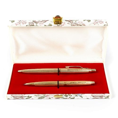 A 9ct gold ballpoint pen set. Comprising two examples each having engine turned bodies with personal