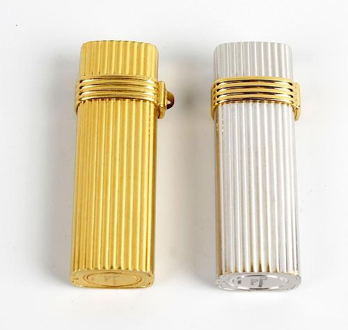 A pair of lighters by Christian Dior. Comprising a gold plated example, and another base metal, both
