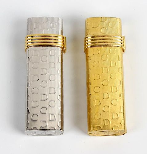 A pair of lighters by Christian Dior. Comprising a white gold plated example stamped Plaque OR G, an