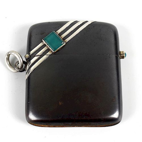 An Art Deco decorated gun-metal vesta case. Of oblong form and shaped for the hip, inset with a rect
