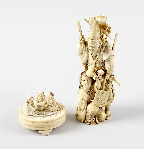 A 19th century carved ivory okimono, modelled as a male laden with sword and other tools, a female a
