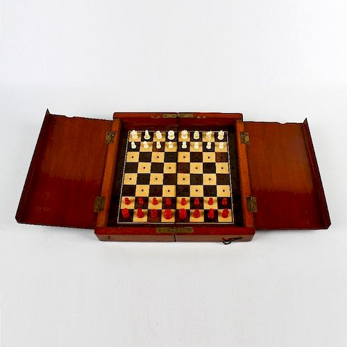A mahogany-cased travel chess set. Early 20th century, the folding board with internal covers enclos