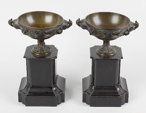 A pair of bronze pedestal urns. Each of shallow form with twin phoenix handles, the exterior decorat