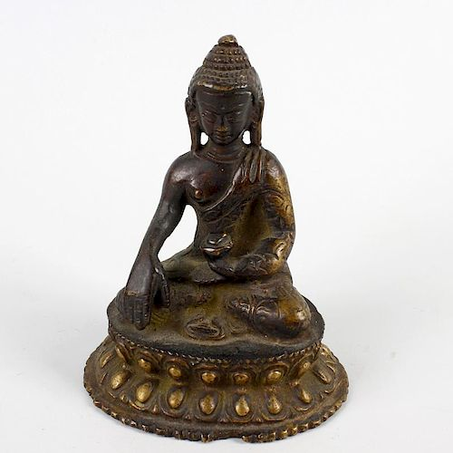 A South East Asian cast bronze figure of a Buddha. Modelled in seated Lotus position holding a vesse