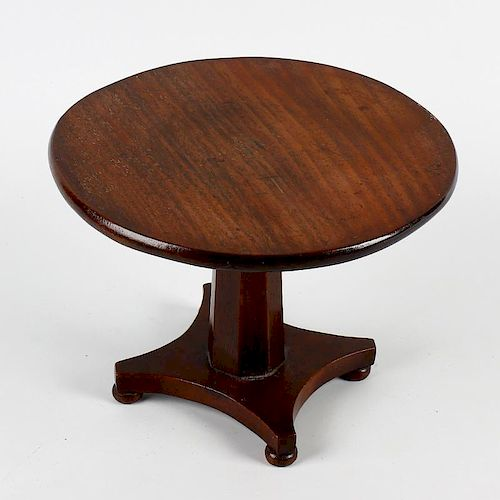 A William IV/early Victorian mahogany miniature centre table. The one-piece circular fixed top on a