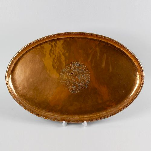 An Arts and Crafts oval copper dish by Hugh Wallis, the central panel, decorated with an engraved de