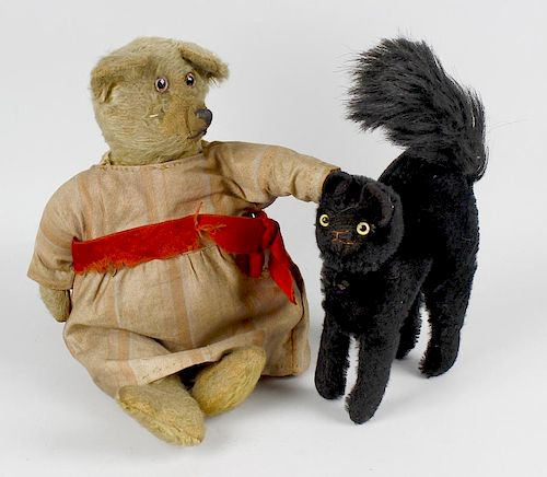 A small group of toys. Comprising a straw-filled plush teddy bear with glass eyes, arm pads and seam