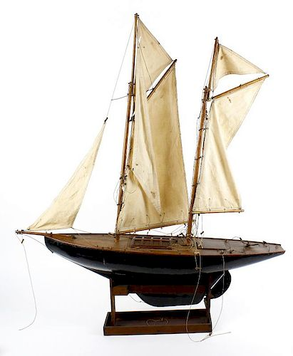 A wooden plank on frame model yacht, the twin masts with stitched cloth sails above a simulated plan