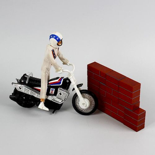A box containing an Ideal Evel Knievel scramble van in original box, other Evel Knievel items, a mix