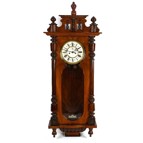 A Gustav Becker walnut and mahogany cased Vienna style wall clock. The shaped pediment above a shape
