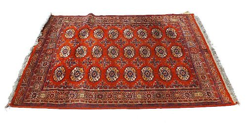 Two Eastern rugs. Comprising a Belouch/Tekke Turkoman type with three rows of eight guls on a tomato