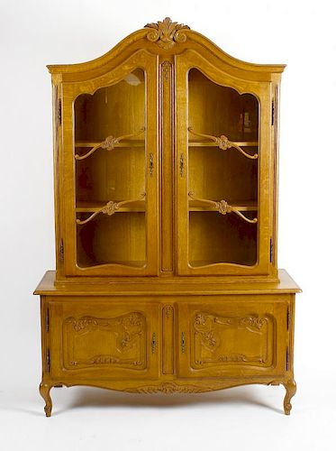 A reproduction oak display cabinet. The upper section with carved scrolled pediment above twin glaze