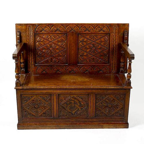 An early 20th century oak 'monk's bench'. Of typical form, the rectangular turn-over top with lunett