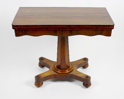 An early Victorian rosewood fold-over pedestal card table. The rounded oblong top enclosing a circul