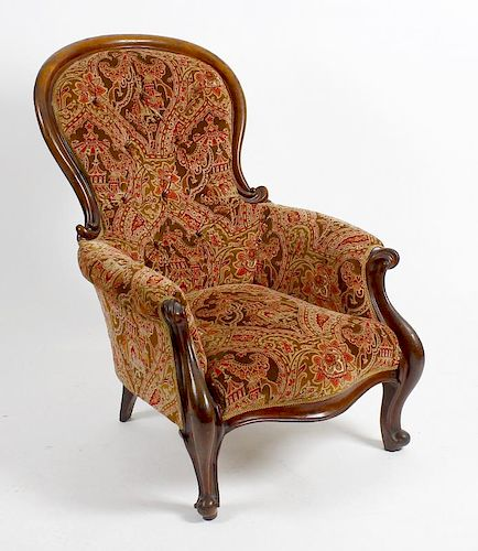 A mid 19th century mahogany-framed spoon-back easy chair. The deep-buttoned spoon back, scroll arms