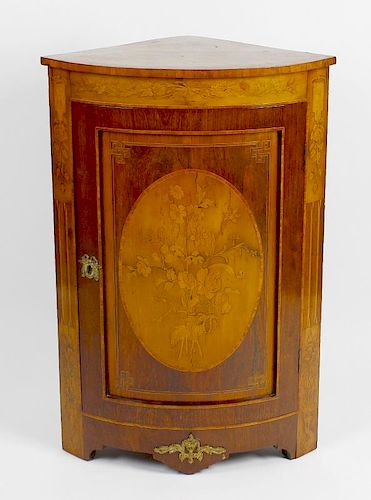 An early 20th century floor standing corner cabinet. The front with curved panelled door, inlaid wit