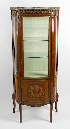 A 20th century French bow front vitrine or display cabinet Having a pierced gilt metal gallery over