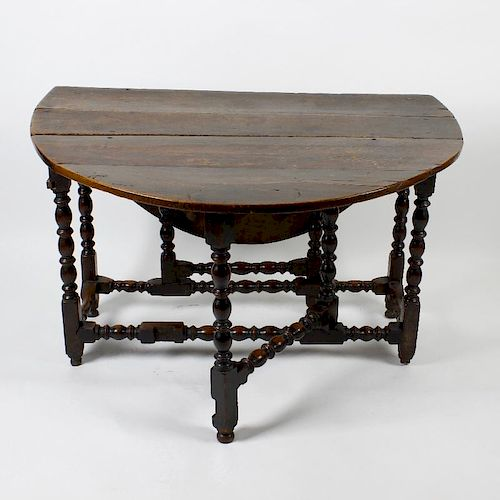 A late 17th century oak gateleg table. Having a two-plank top with oval flaps on bobbin- and ring-tu