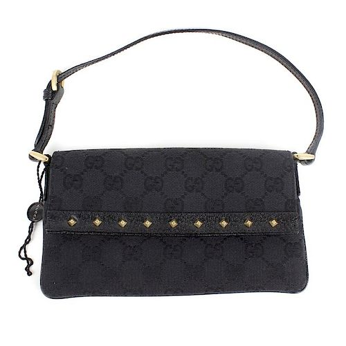 3d241e6d1bb GUCCI - a small studded shoulder bag. Featuring a black canvas exterior  with GG motif