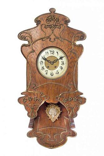 * An Art Nouveau Oak and Gilt Metal Mounted Wall Clock, Height 34 x width 16 3/8 inches.