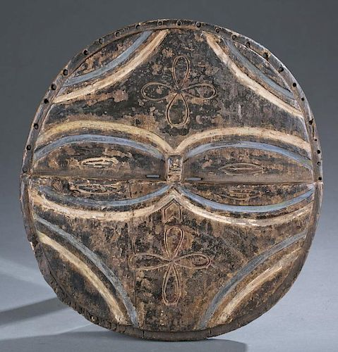 Round wood mask with oval shaped eyes.