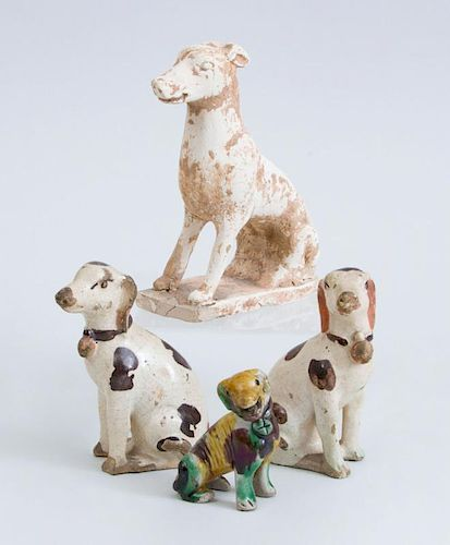 TANG TYPE UNGLAZED POTTERY FIGURE OF A SEATED HOUND, A GLAZED SEATED HOUND AND A PAIR OF SPOTTED SEATED HOUNDS