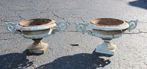 A pair of mini cast iron double handled garden urns.