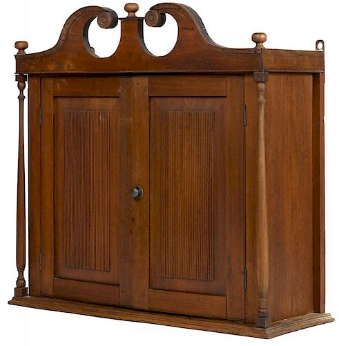 Pennsylvania or New Jersey walnut hanging cupboard, early 19th c., with a broken arch crest and re
