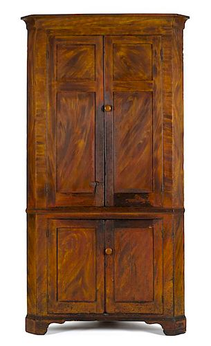 Painted pine one-piece corner cupboard, early 19th c., retaining its original orange and yellow gr
