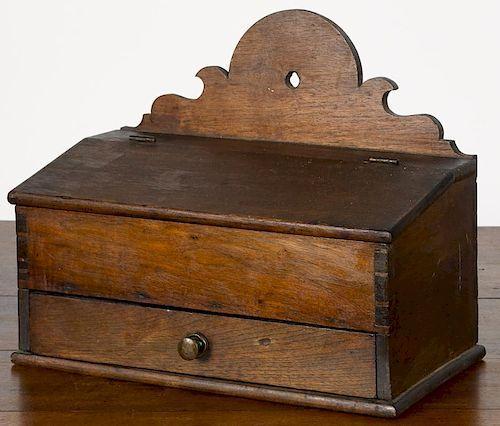 Pennsylvania walnut hanging box, 19th c., with scalloped backsplash, slant lid and single drawer,