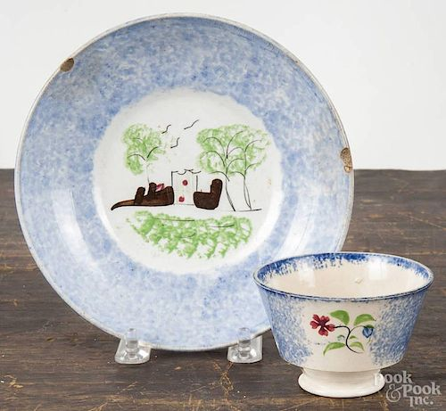 Blue spatterware fort saucer, 19th c., together with a blue spatterware cup with floral decoration.