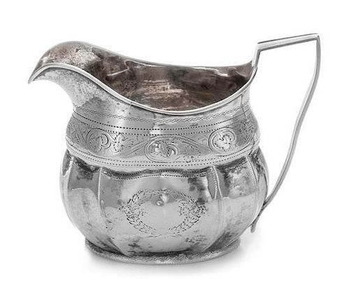 An Irish George III Silver Creamer, Robert Breading, Dublin, 1805, the bright-cut volute decorated collar above the lobed pan