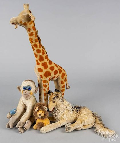 Four Steiff plush animals, to include a giraffe, 30 1/2'' h., a monkey, a dog, and a lion.