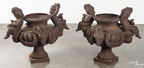 Pair of cast iron putti and rams head garden urns
