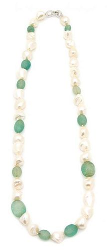 A Baroque Pearl and Carved Green Beaded Necklace Length 28 inches.