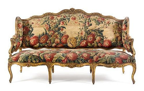 * A Louis XV Giltwood Canape a Oreilles Height 45 1/8 x width 76 x depth 25 1/2 inches.