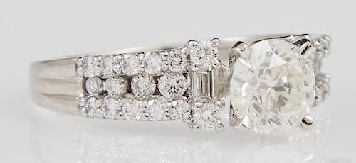 Lady's Platinum Dinner Ring, with a central 1.14 carat round diamond flanked by diamond mounted lugs, the shoulders of the ri