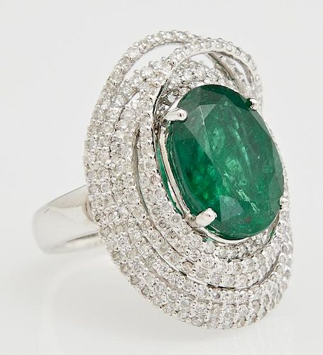 Lady's 18K White Gold Dinner Ring, with an oval 6.95 carats emerald centering swirled concentric bands of round diamonds, tot