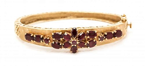 * A 14 Karat Yellow Gold and Garnet Bangle Bracelet, 12.90 dwts.