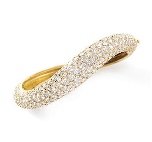An 18 Karat Yellow Gold and Diamond Pave Bangle Bracelet, 24.95 dwts. in an asymmetric curved design, containing 289 round brill