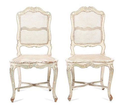 A Pair of Louis XV Style Carved and Painted Caned Back and Seat Side Chairs Height 38 1/2 inches.