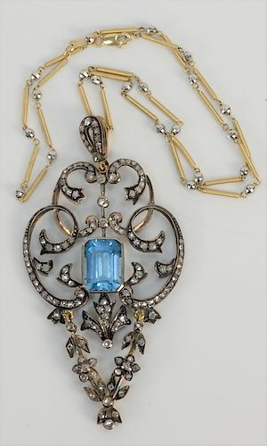 18 karat gold and silver lavalier pendant with center emerald cut blue stone measuring 11 x 14 mm, surrounded by approximately 1 ct....