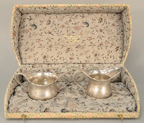 Tiffany & Co. sterling silver sugar bowl and creamer,  both having hand hammered finish and scrolling handles, marked: Tiffany & Co....
