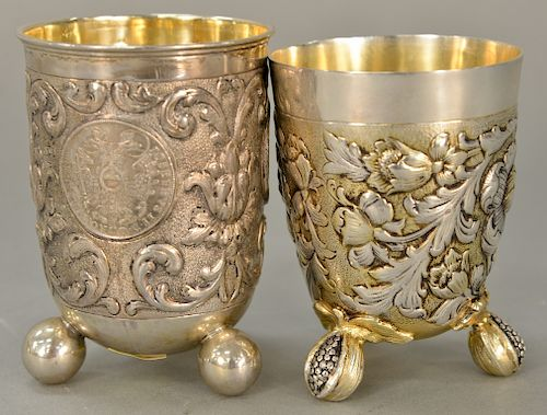 Two German silver beakers, each on three feet, one mounted with three large silver coins, one with floral chased body with gilt high...
