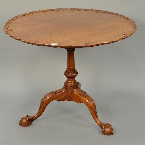 Margolis mahogany piecrust tip table with carved top,  on fluted and carved shaft, set on tripod base ending in ball and claw feet. ...